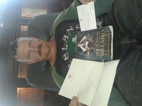 Photo of Sir John L Greene with his book and letters from President Higgins and Queen Elizabeth